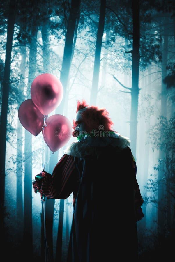 Läskiga clowner som rymmer ballonger i en skog fotografering för bildbyråer