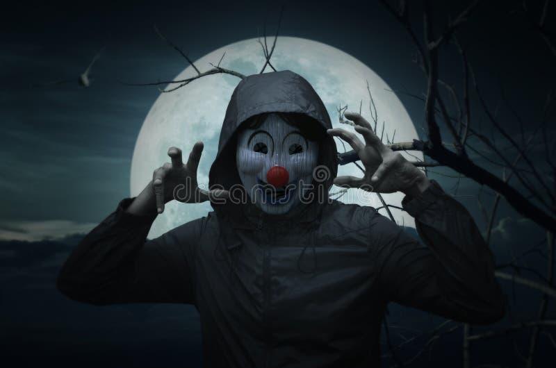 Läskigt ont clownkläderomslag över fågel, dött träd, månen och spoo royaltyfria foton