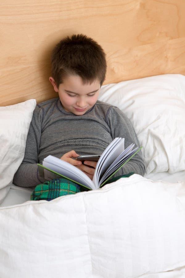 Läsning en boka eller en Texting royaltyfri fotografi