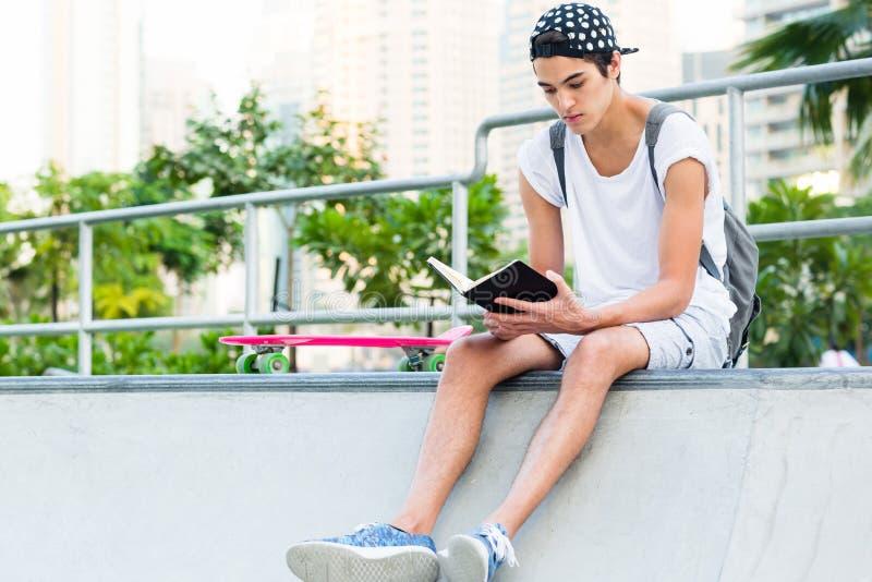 Läsning för den unga mannen på skateboarden parkerar fotografering för bildbyråer