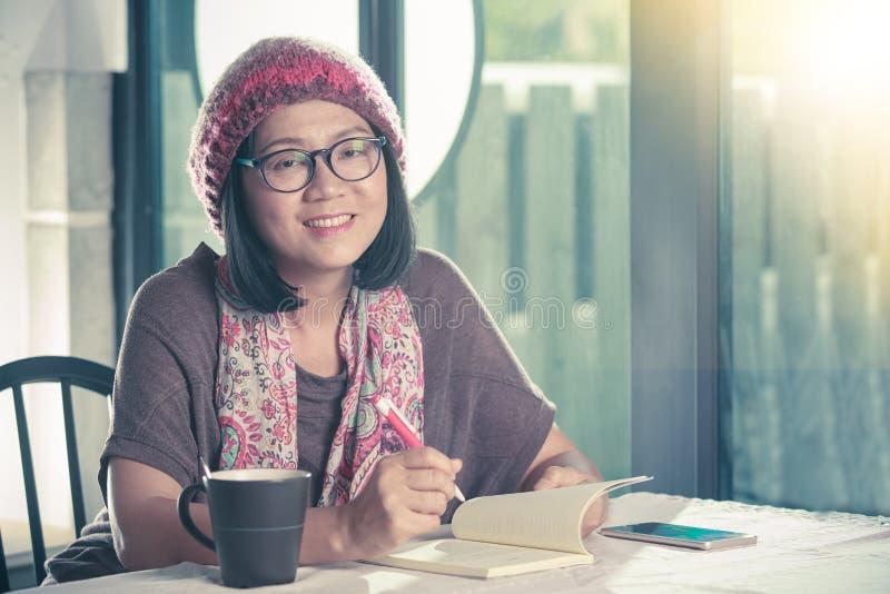 läsning för gammal asiatisk kvinna för 40-talår avslappnande och drickakaffe I arkivfoton