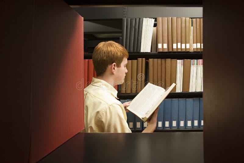 Läsning för manlig student i arkivet royaltyfri bild