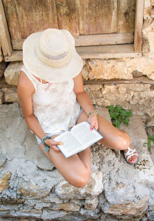 Läsning för trendig kvinna i en gammal stad royaltyfri fotografi