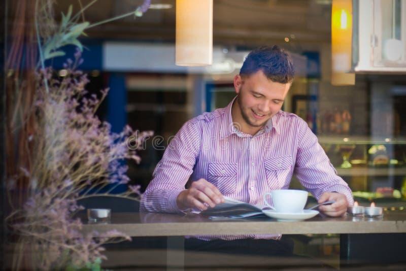 Läsning för ung man och drickakaffe royaltyfri foto
