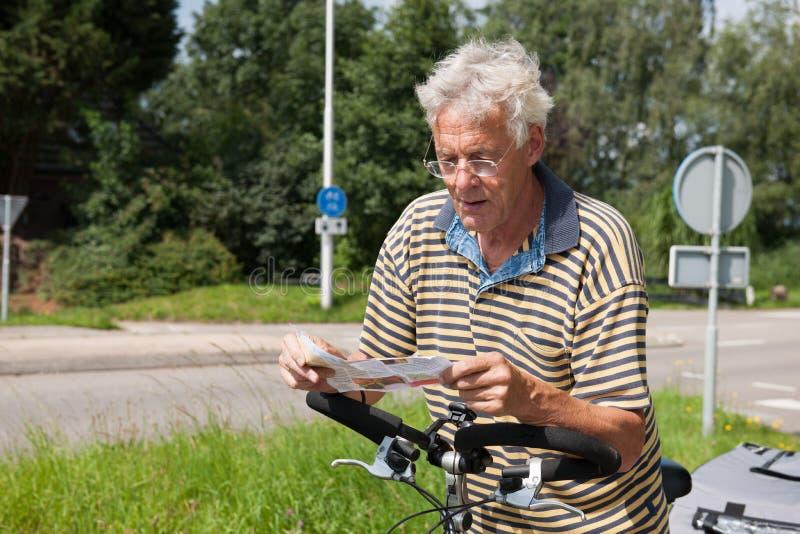 Läsning som rutten kartlägger vid cyklist fotografering för bildbyråer
