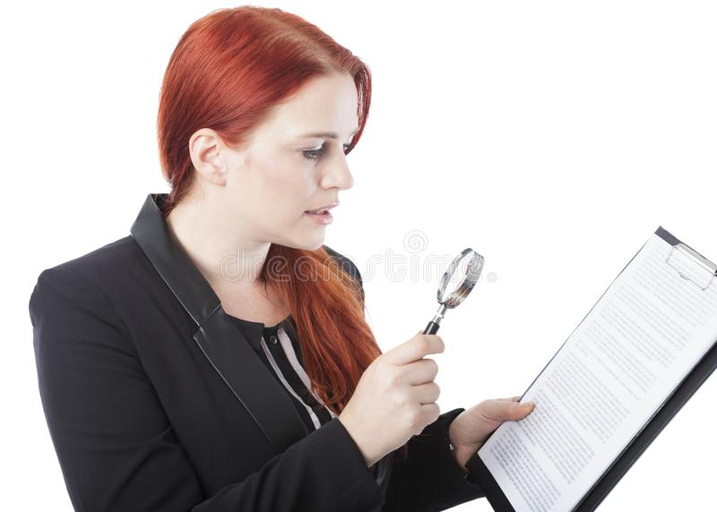 Läsningdokument för ung kvinna med förstoringsglaset royaltyfri bild