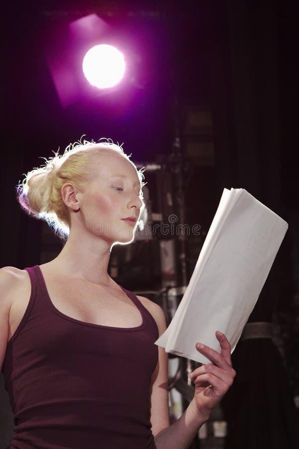 Läsningskrift för ung kvinna på etapp royaltyfri bild