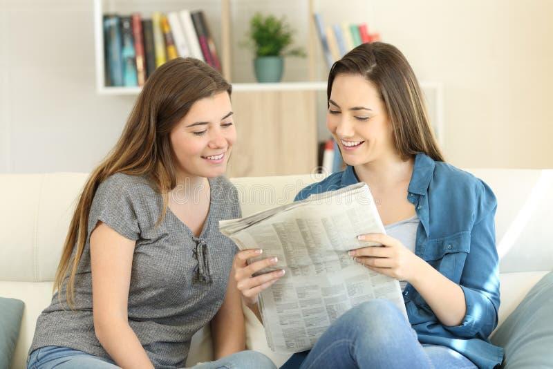 Läsningtidning för två vänner tillsammans hemma arkivbild