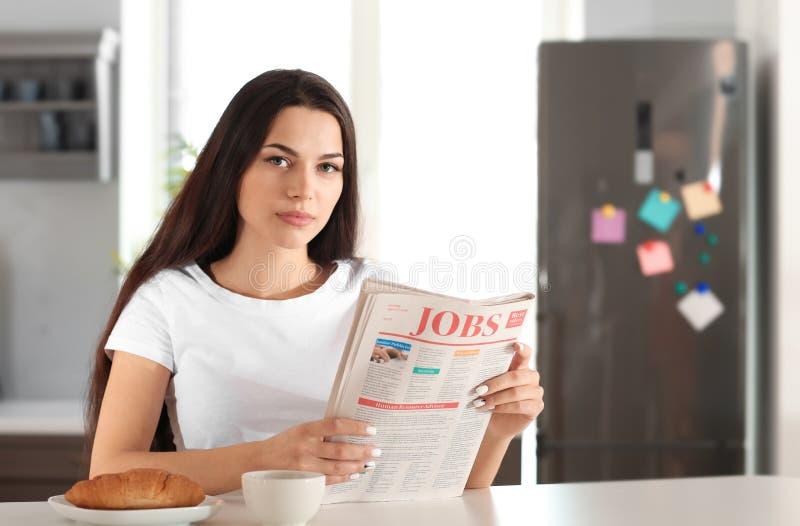 Läsningtidning för ung kvinna i kök royaltyfri fotografi