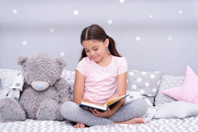 Läst för sömn Flickabarnet sitter säng med den lästa boken för nallebjörnen Ungen förbereder sig att gå att bädda ned Angenäm tid arkivbilder