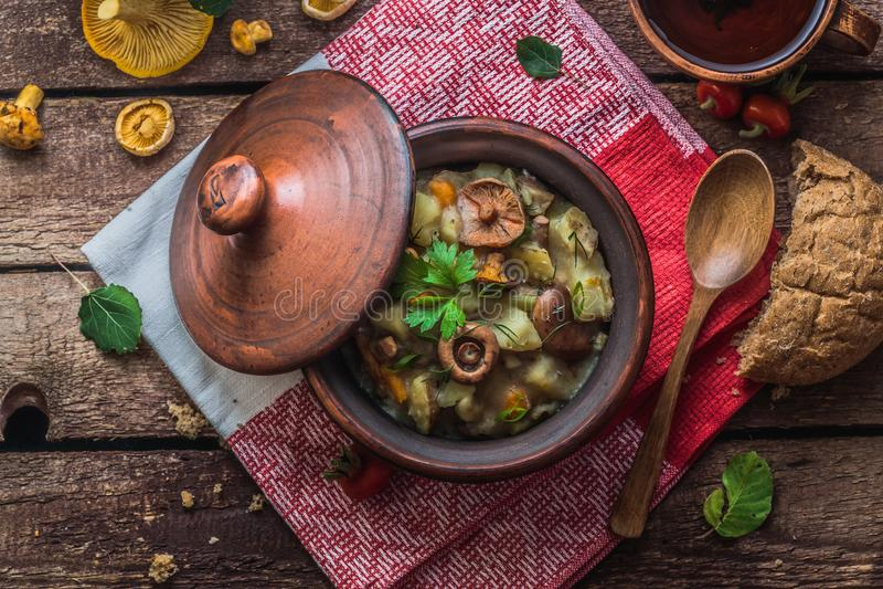 Lät småkoka potatis och champinjoner i en lerakruka, lantlig stil arkivfoto