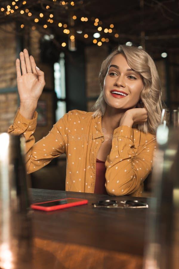 Lätt berusad ung kvinna som vinkar på någon i stång arkivfoton