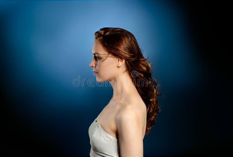 Lätt modeporträtt Ung kvinna i blå väggbakgrund royaltyfri foto
