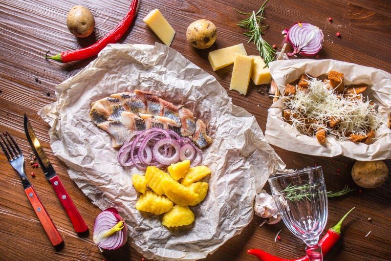 Lätt rimmad sill med kokta potatisar, lökar och krutonger med ost royaltyfria bilder