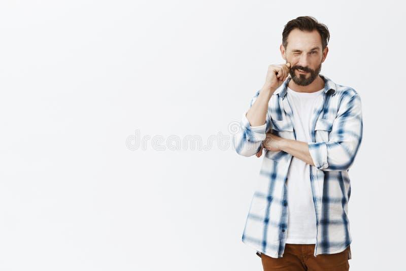 Lätt som en två tre Stilig säker och flirty vuxen man med skägget, rullande spets av mustaschen på fingret och stirra arkivfoto
