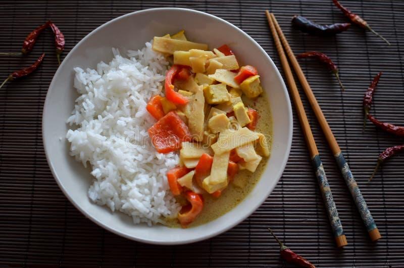 Lätt vegetarisk thai grön currysås med basmati ris som göras från röda peppar, chilipeppar, tofuen och bambuskott royaltyfri fotografi
