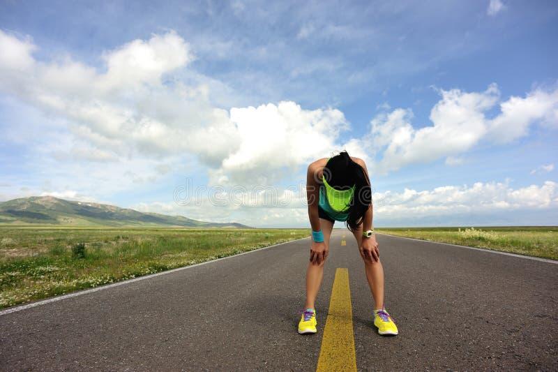 Läufer, der eine Pause macht, nachdem auf Spur stark laufen lizenzfreie stockfotos