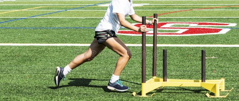 Läufer, der einen gelben Schlitten auf einem Rasenfeld drückt lizenzfreies stockbild