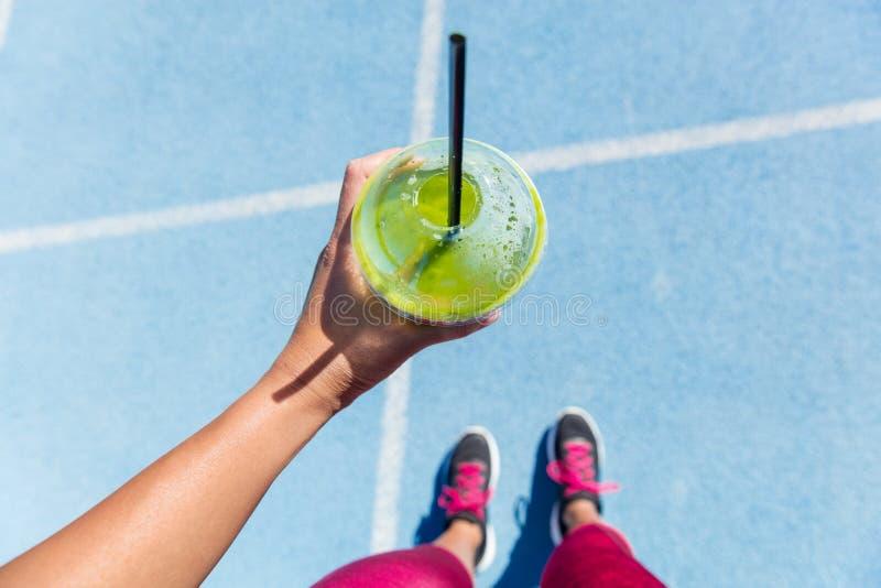 Läufer, der einen grünen Smoothie auf Laufbahn trinkt stockfotos