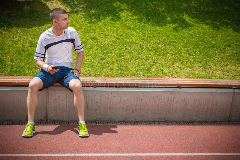 Läufer, der nahe bei der Laufbahn sitzt stockfotografie
