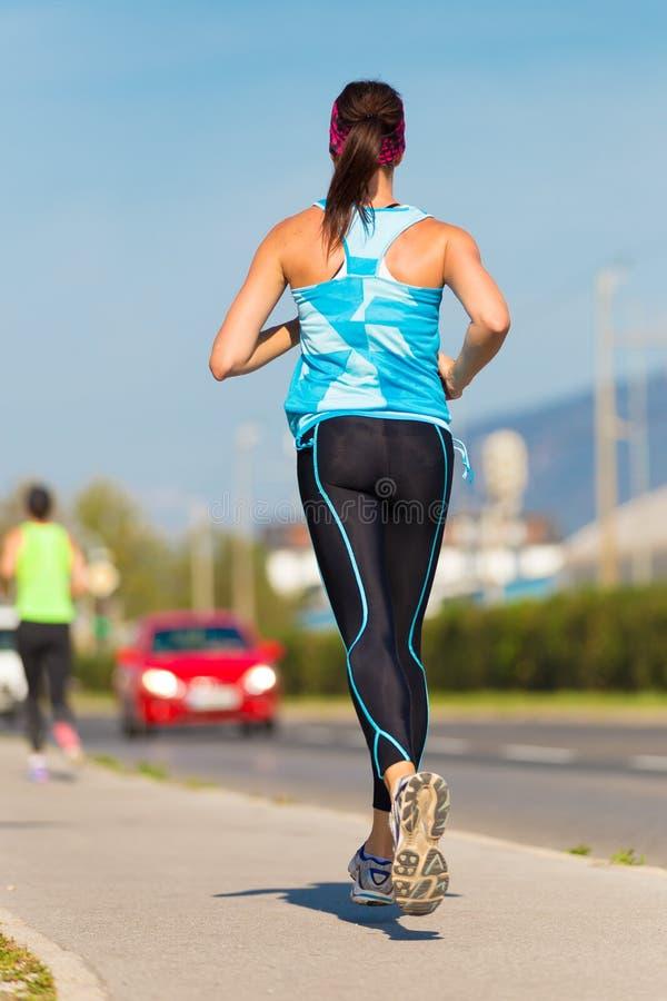 Läufer des jungen Mädchens auf der Straße lizenzfreie stockfotos