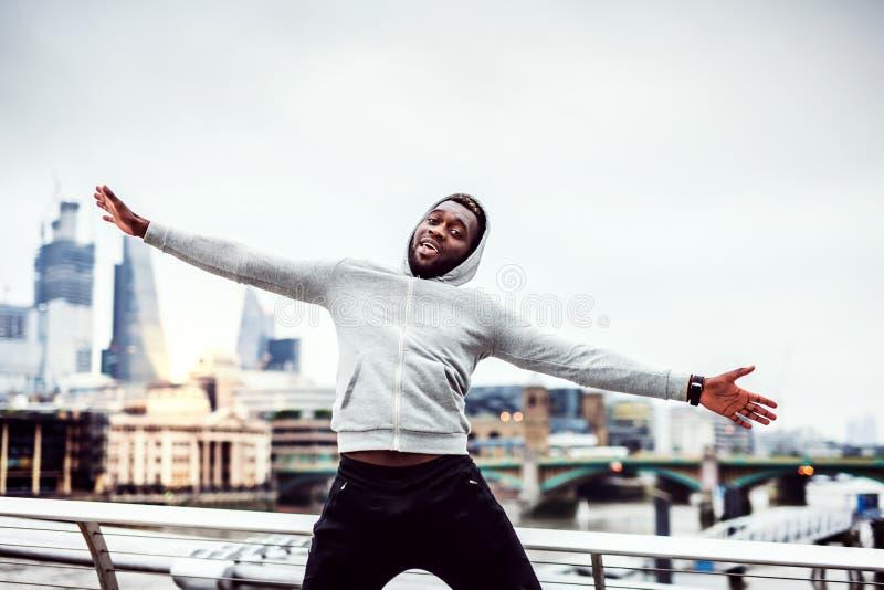 Läufer des schwarzen Mannes auf der Brücke in einer Stadt, stillstehend und haben Spaß stockfotografie
