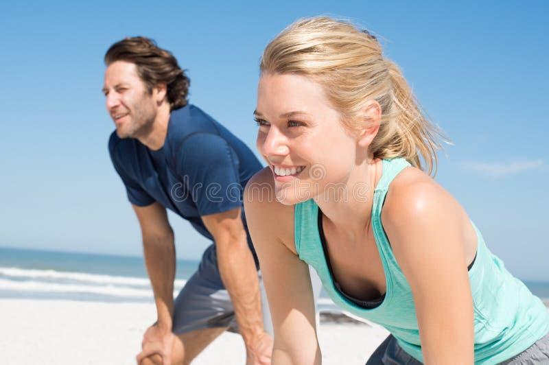 Läufer, die am Strand stillstehen stockbilder