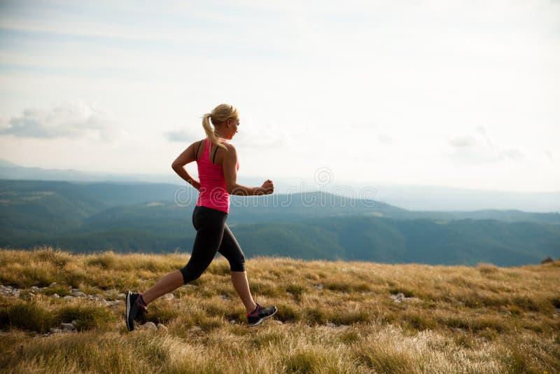 Läufer - Frau lässt Kundenberaterinland auf einem Weg im Frühherbst laufen stockbild