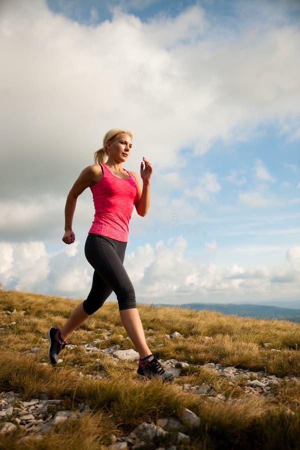 Läufer - Frau lässt Kundenberaterinland auf einem Weg im Frühherbst laufen stockfoto