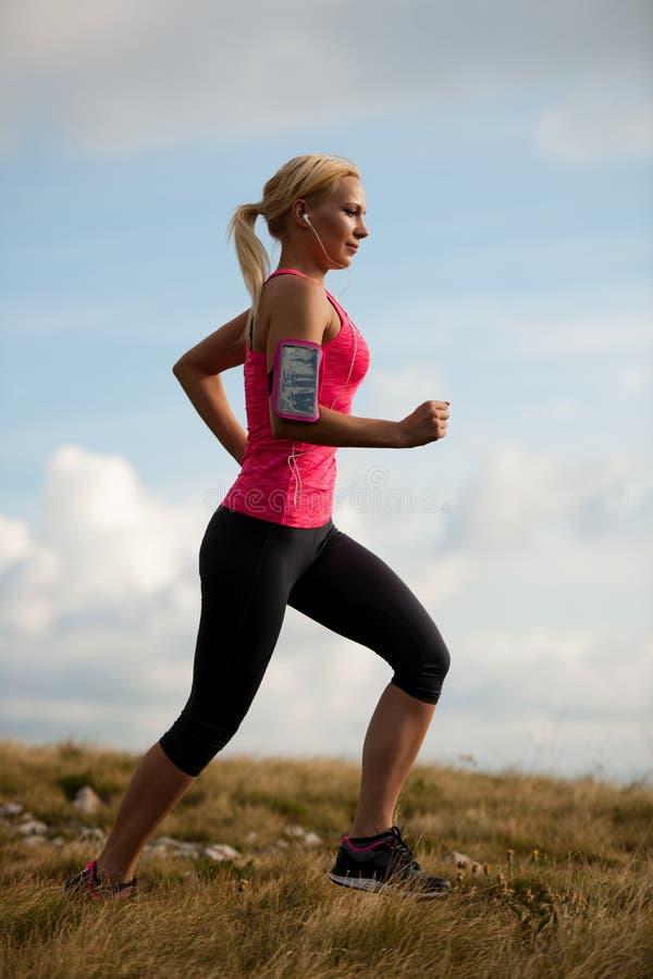 Läufer - Frau lässt Kundenberaterinland auf einem Weg im Frühherbst laufen stockfotografie