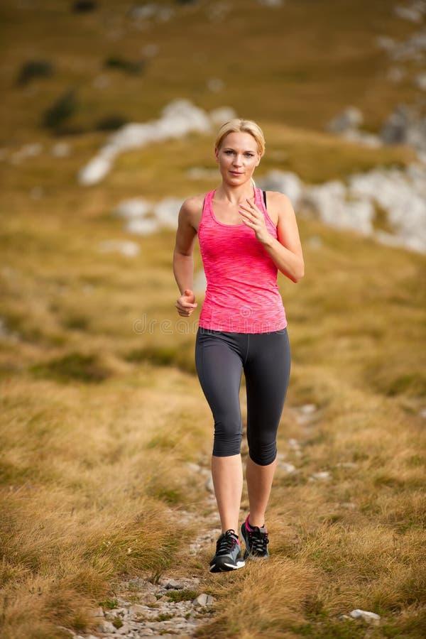 Läufer - Frau lässt Kundenberaterinland auf einem Weg im Frühherbst laufen lizenzfreies stockfoto