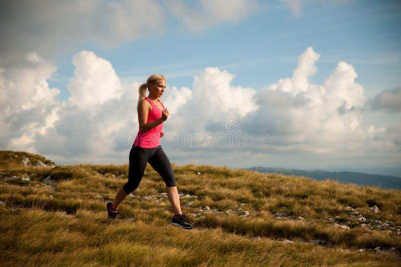 Läufer - Frau lässt Kundenberaterinland auf einem Weg im Frühherbst laufen lizenzfreie stockbilder