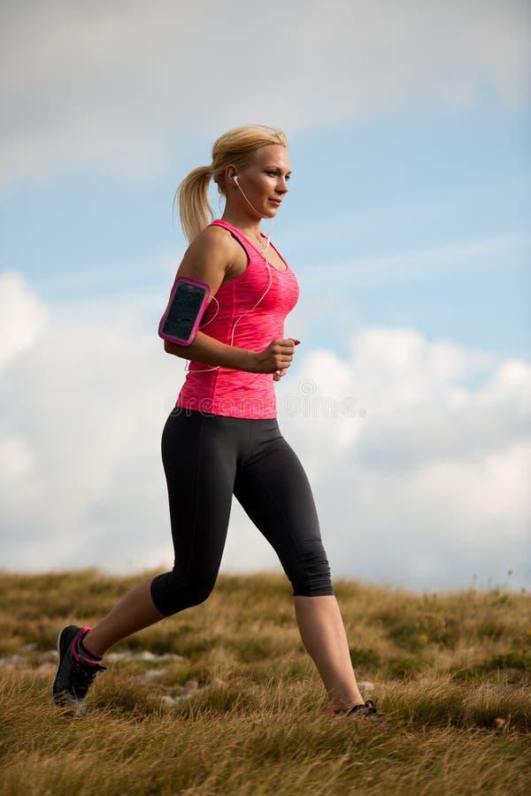 Läufer - Frau lässt Kundenberaterinland auf einem Weg im Frühherbst laufen lizenzfreie stockfotos