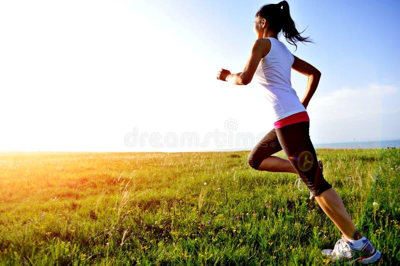 Läuferathlet, der auf Gras läuft lizenzfreie stockfotos
