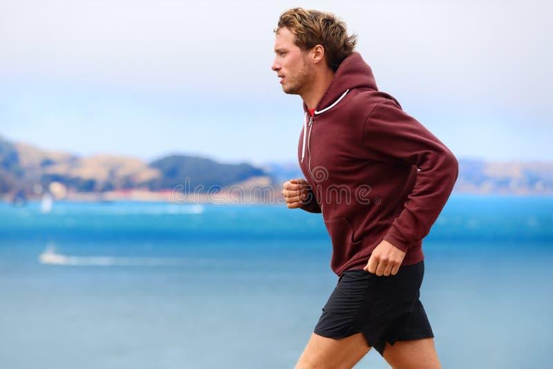Läuferathletenmann, der in Sweatshirt läuft stockbild