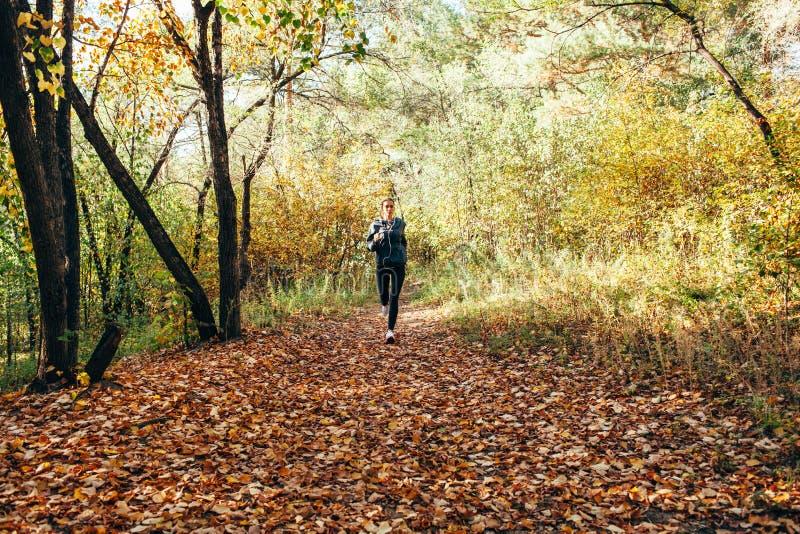Läuferfrau, die im Herbstpark rüttelt stockfotos