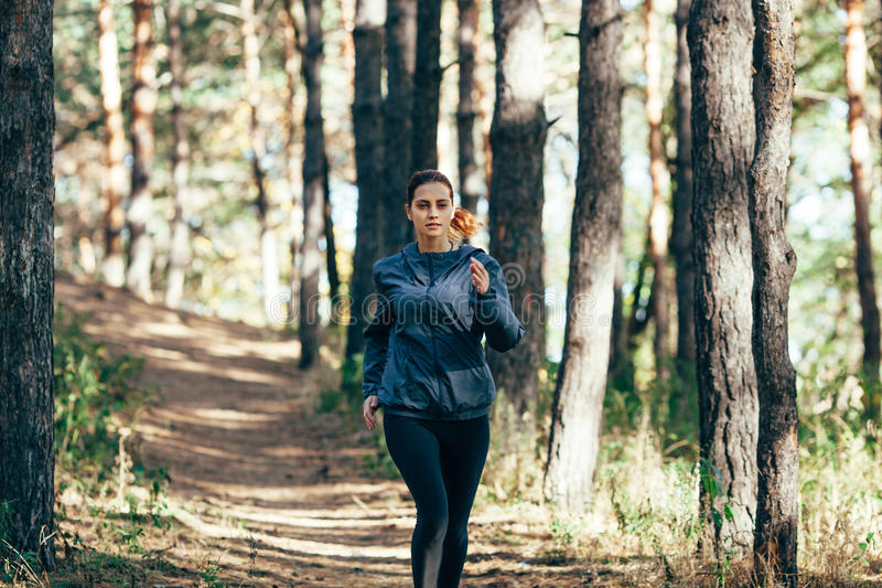 Läuferfrau, die im Herbstpark rüttelt stockfoto