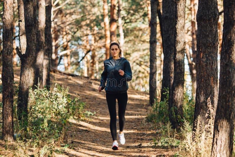 Läuferfrau, die im Herbstpark rüttelt stockfotografie