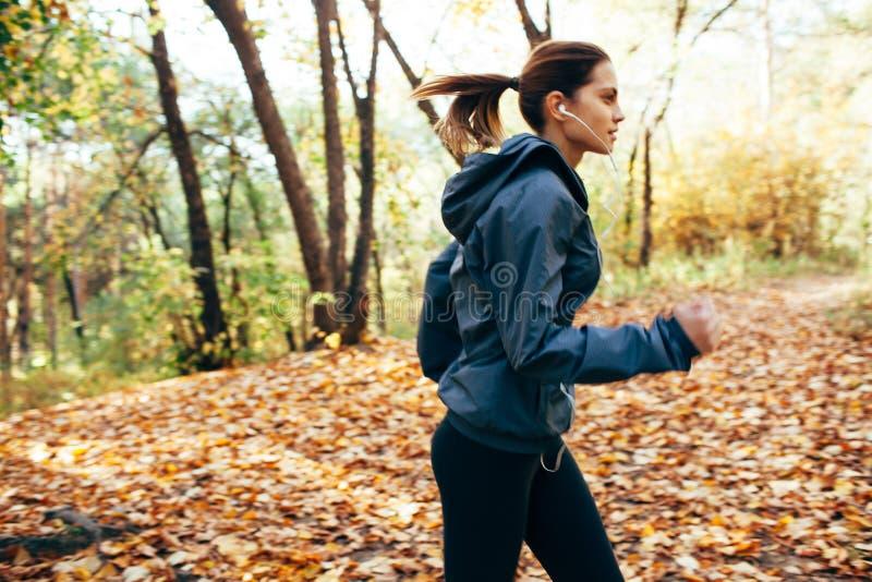 Läuferfrau, die im Herbstpark rüttelt Bewegungsunschärfe-Effekt stockfotos