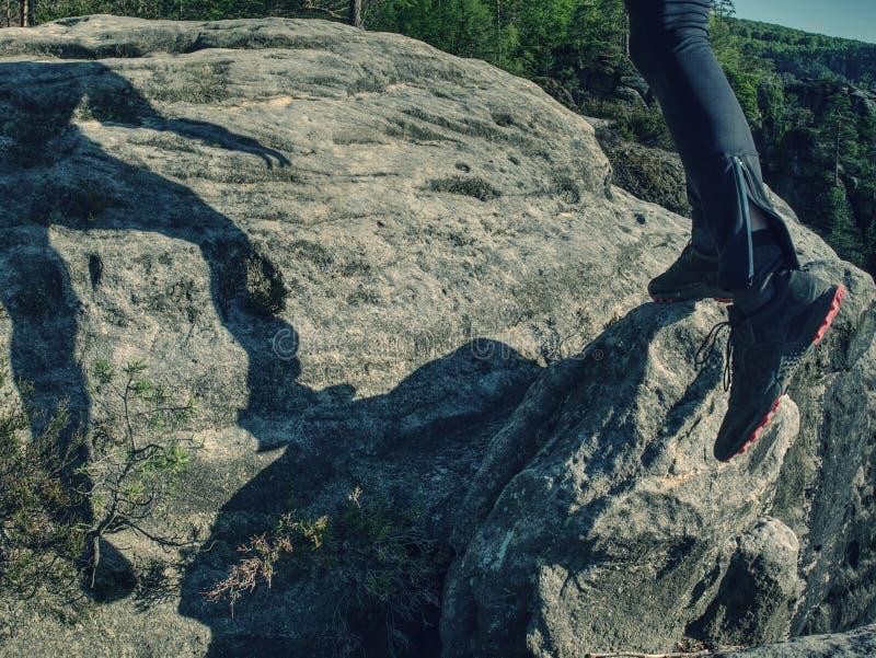 Läuferkörper und -schatten auf Sandsteinfelsen Laufender Mann stockfotografie