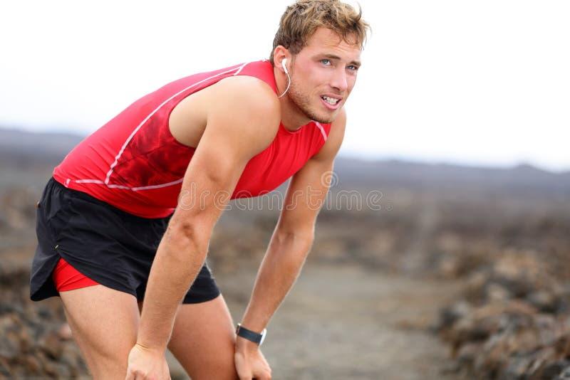 Läufermann, der bei der Musik nachdem dem Laufen liegt stockbild