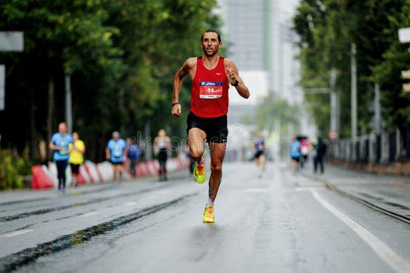 Läufersieger der Marathonlaufenstraße im Regen stockbilder