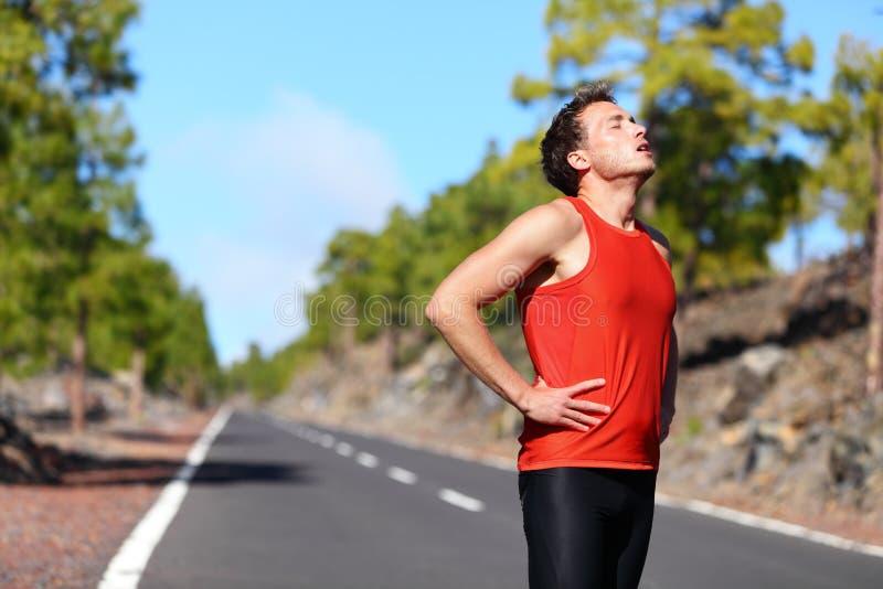 Läuferstillstehen ermüdet erschöpft nachdem dem Laufen stockfotografie