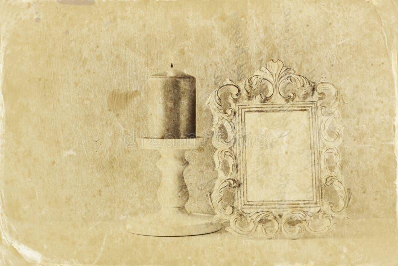 Låg nyckel- bild av den antika klassiska ramen för tappning och bränningstearinljus på trätabellen retro filtrerad bild för fotos royaltyfria bilder