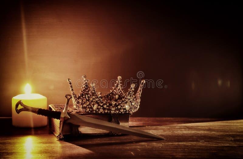 låg nyckel- bild av den härliga drottningen/det konungkronan och svärdet medeltida period för fantasi Selektivt fokusera arkivbild