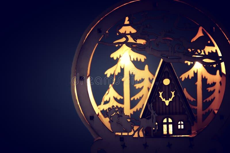 Låg nyckel- bild av den magiska julplatsen av den träpinjeskogen, kojan och Santa Claus över släde med deers royaltyfri illustrationer