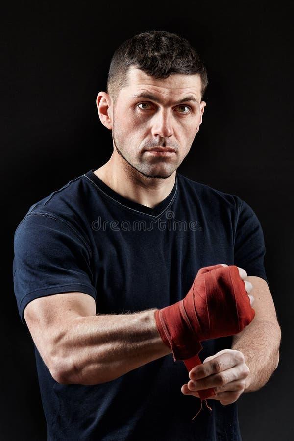Låg nyckel- studiostående av den stiliga muskulösa kämpen som förbereder sig för att boxas på mörk suddig bakgrund arkivfoton