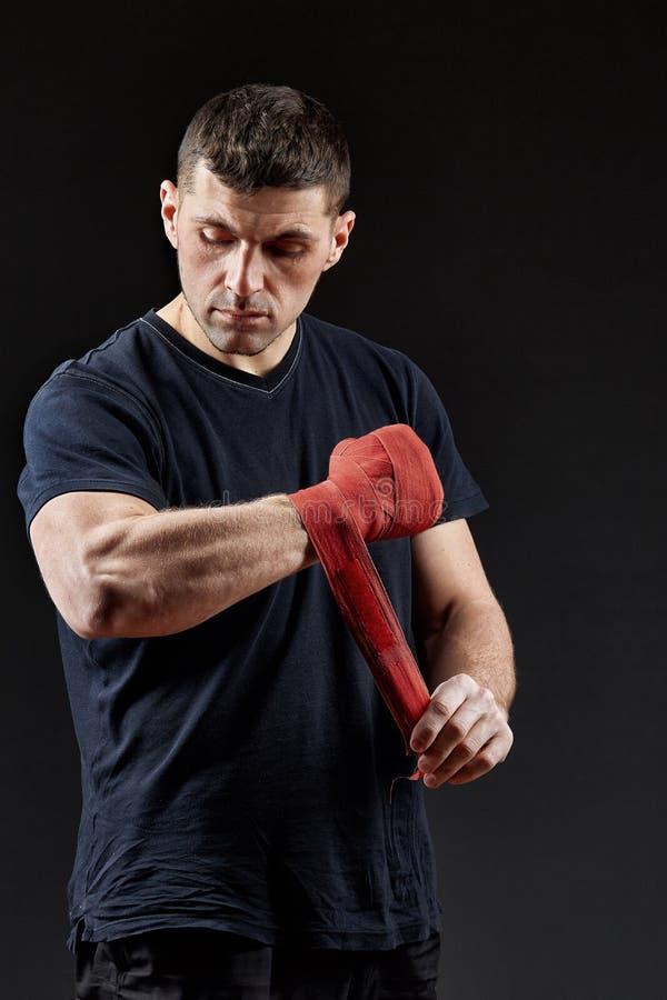Låg nyckel- studiostående av den stiliga muskulösa kämpen som förbereder sig för att boxas på mörk suddig bakgrund royaltyfria bilder