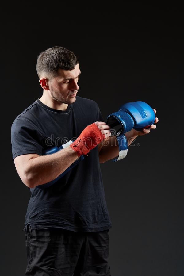 Låg nyckel- studiostående av den stiliga muskulösa kämpen som förbereder sig för att boxas på mörk suddig bakgrund arkivbild