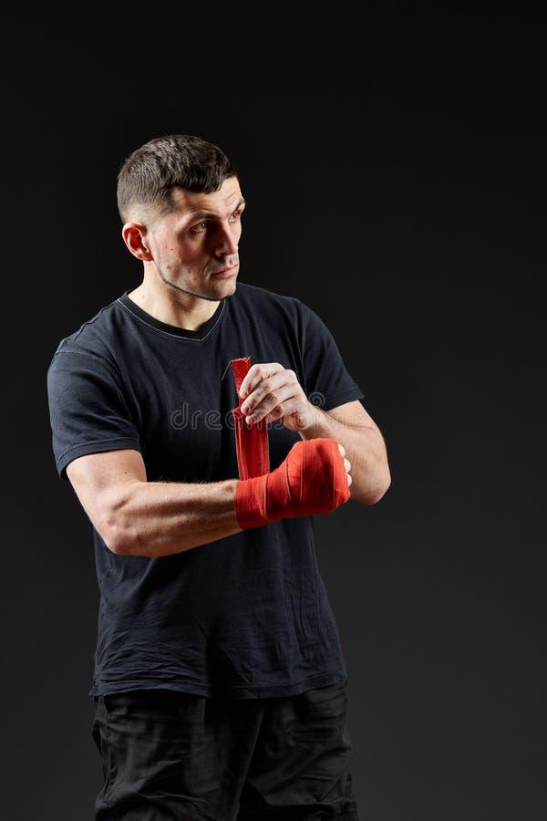Låg nyckel- studiostående av den stiliga muskulösa kämpen som förbereder sig för att boxas på mörk suddig bakgrund royaltyfri bild